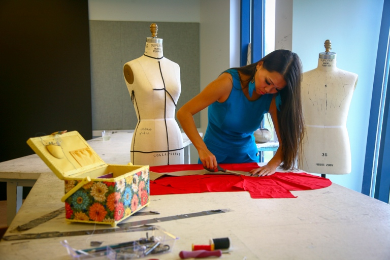 Fashion design student in NYC cutting fabric